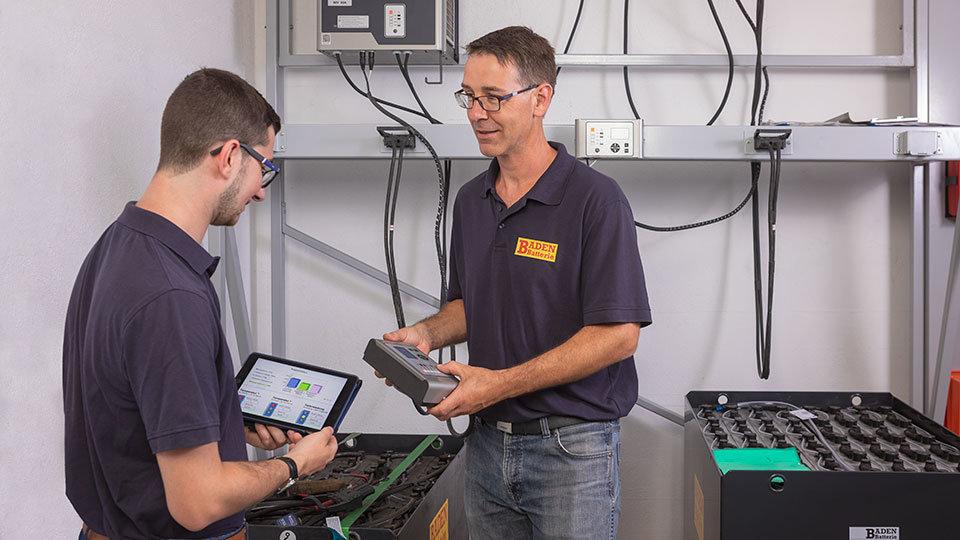 Foto von 2 Mitarbeitern beim Laden einer Batterie