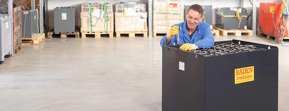 Foto eines Mitarbeiters beim Messen einer Staplerbatterie