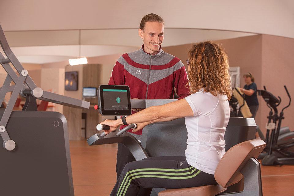 Foto im Fitness-Studio mit Trainer und Kundin