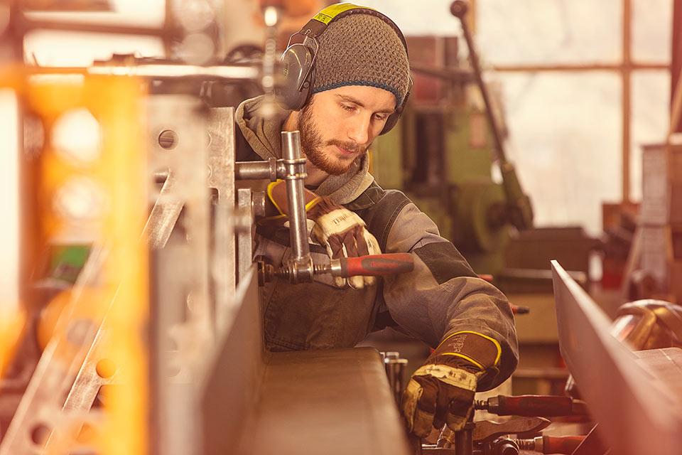 Foto eines Schlossers beim Fixieren eines Stahlteils