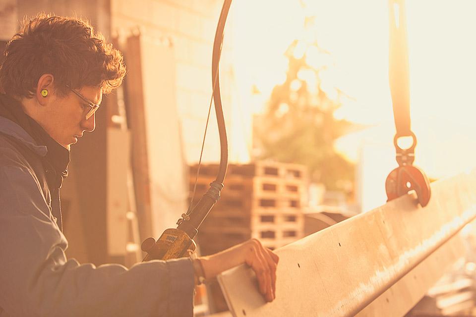 Foto eines Schlossers beim Anheben eines Stahlteils