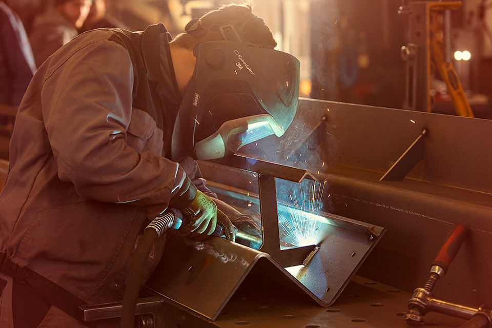 Foto eines Schlossers beim Schweißen von Stahl