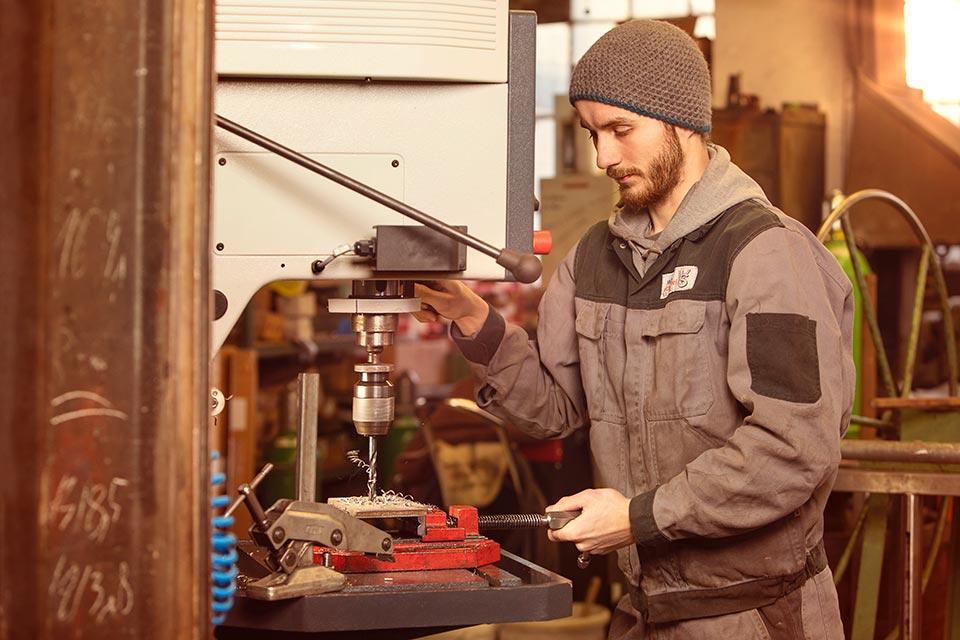 Foto eines Schlossers an einer Metallbohrmaschine
