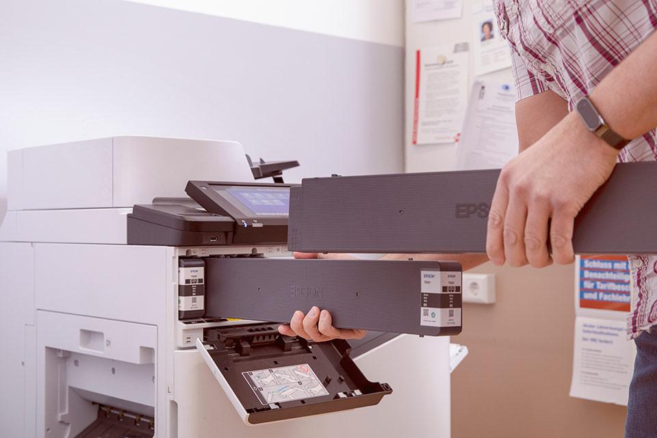 Lehrer beim Auswechseln von Tintenkartuschen am Drucker
